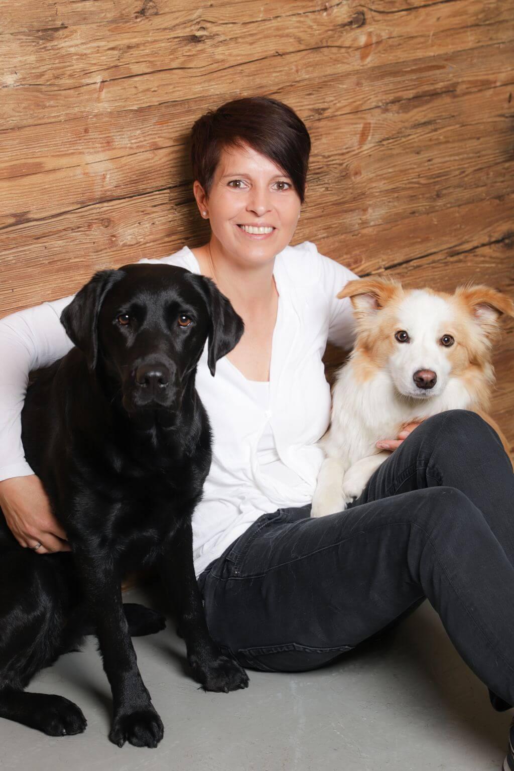 Hundetrainerin Anja Mersdorf sitzt mit ihren Hunden Cookie und Abbey gemütlich auf dem Boden